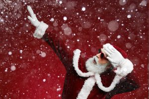 Waist up portrait of funky Santa dancing over red background with snow falling